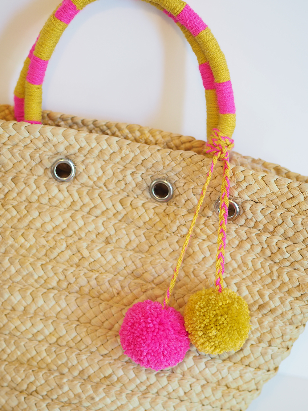 straw basket bag with pom poms