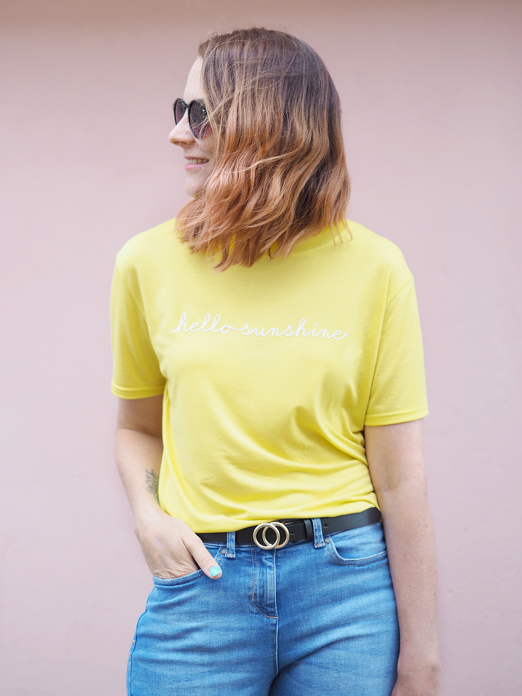 bright colourful outfit yellow tee straw bag with pom poms