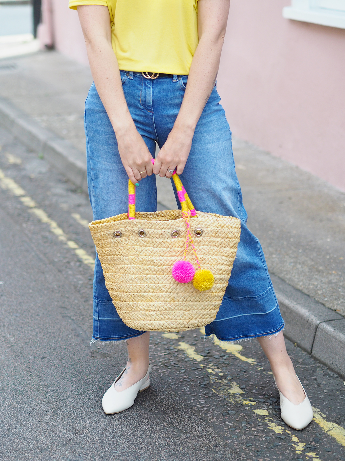 wearing bright colours bright colourful outfit yellow tee straw bag with pom poms