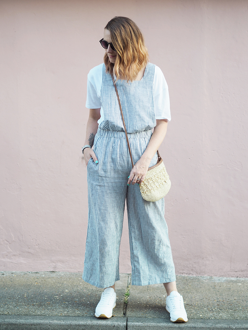 casual jumpsuit outfit with trainers and straw bag