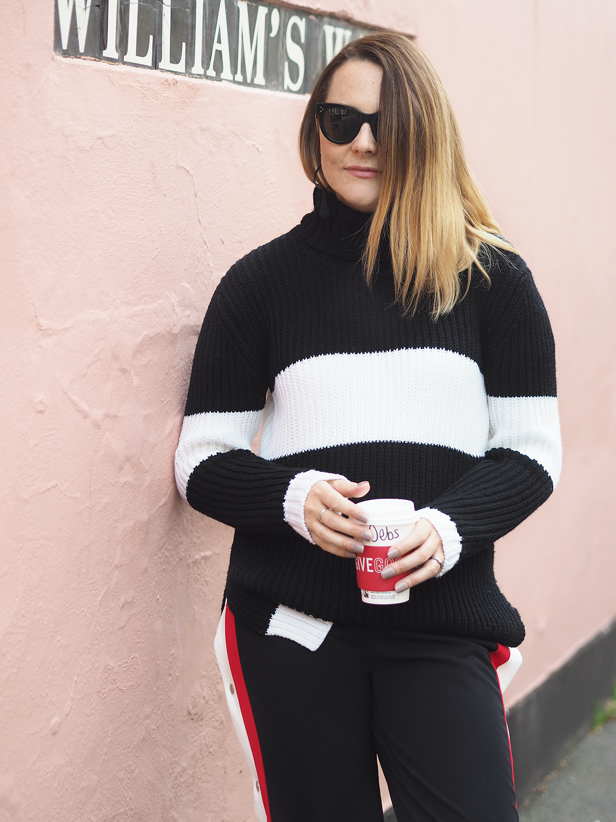 casual dressing outfit with chunky black and white jumper striped trousers and trainers
