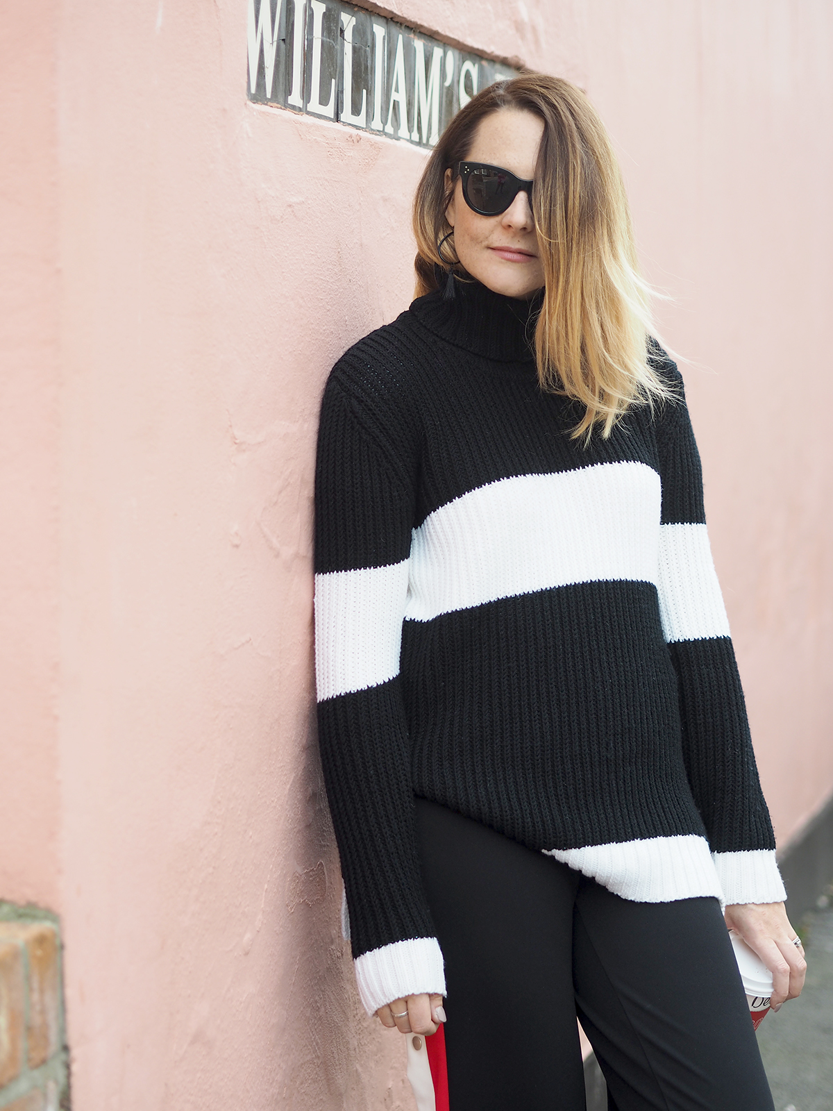 casual outfit with chunky black and white jumper striped trousers and trainers