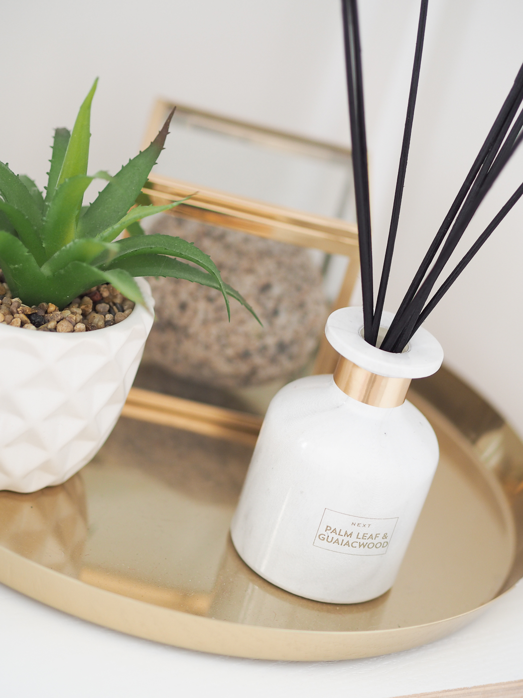 marble reed diffuser and faux succulent shelf styling