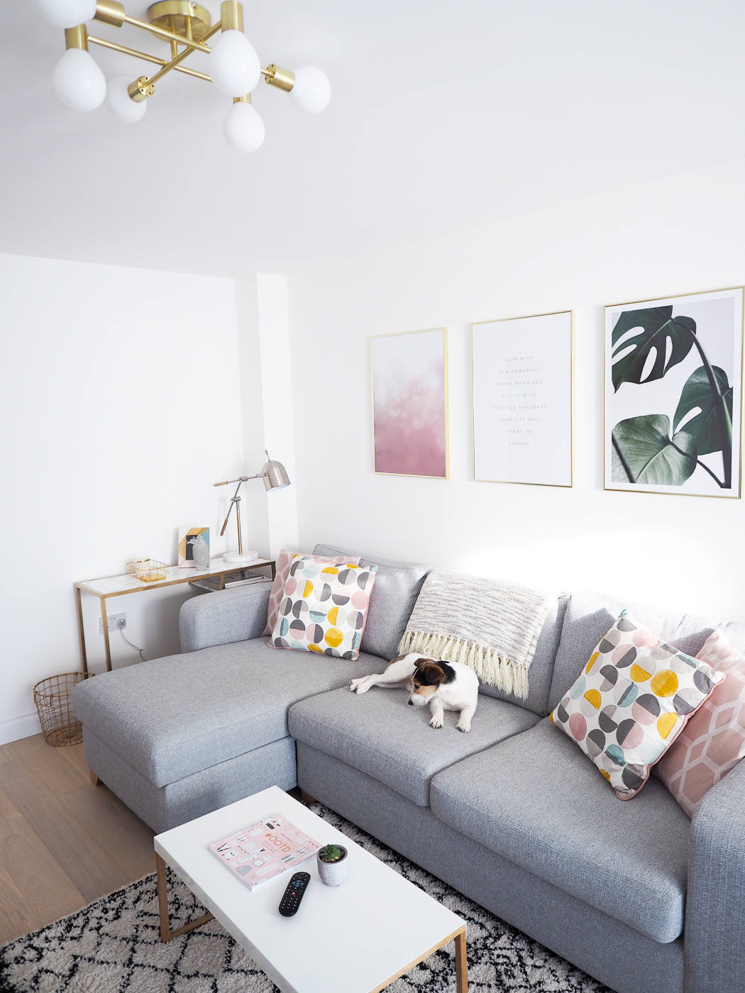 gold ceiling light grey sofa and pink cushions