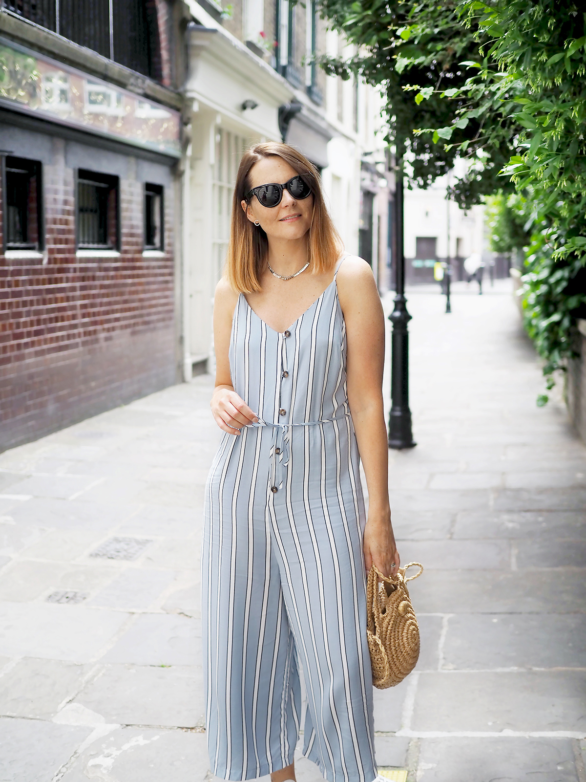 primark jumpsuit with denim jacket and trainers