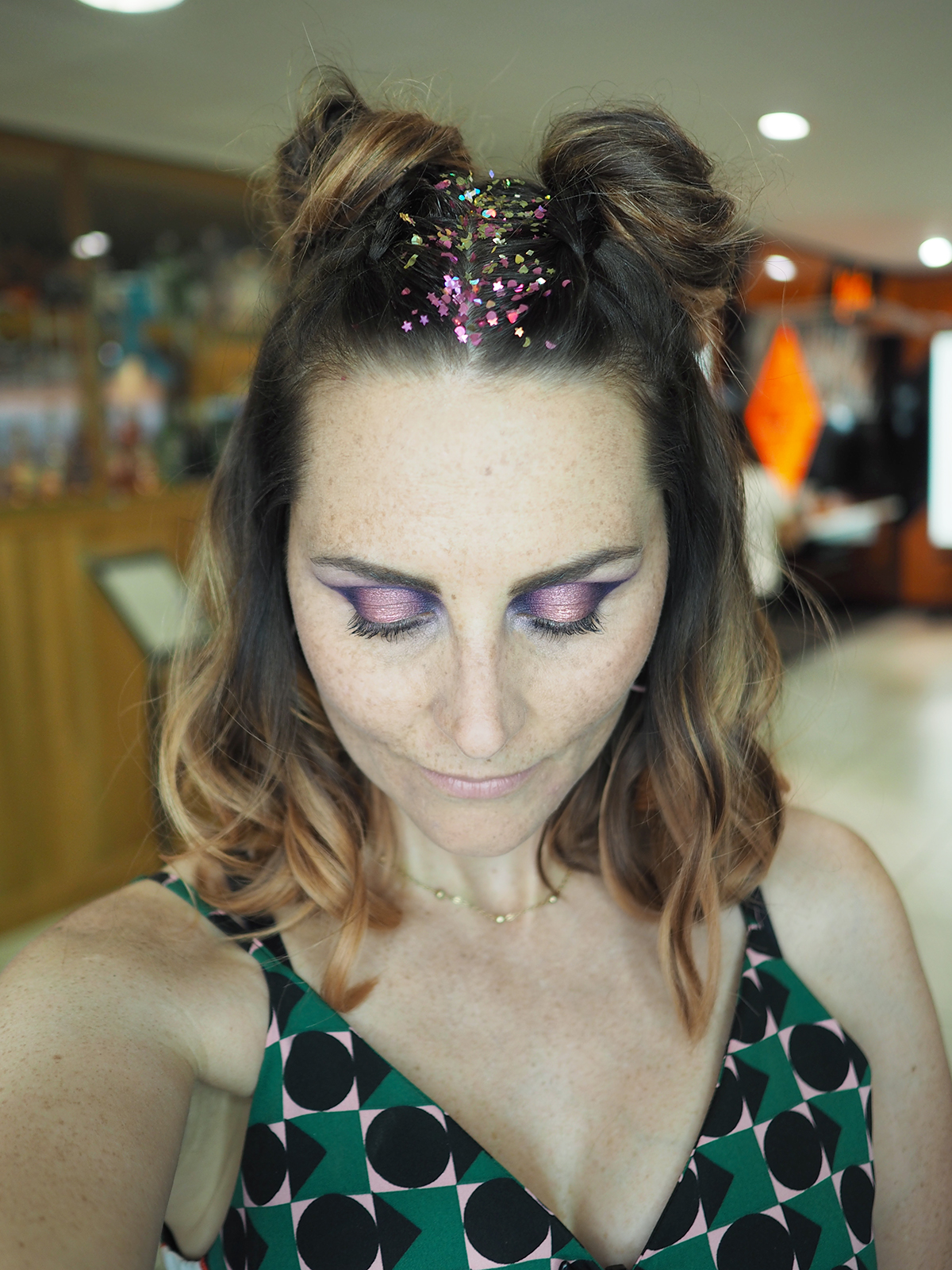 space bun hair with glitter festival makeup