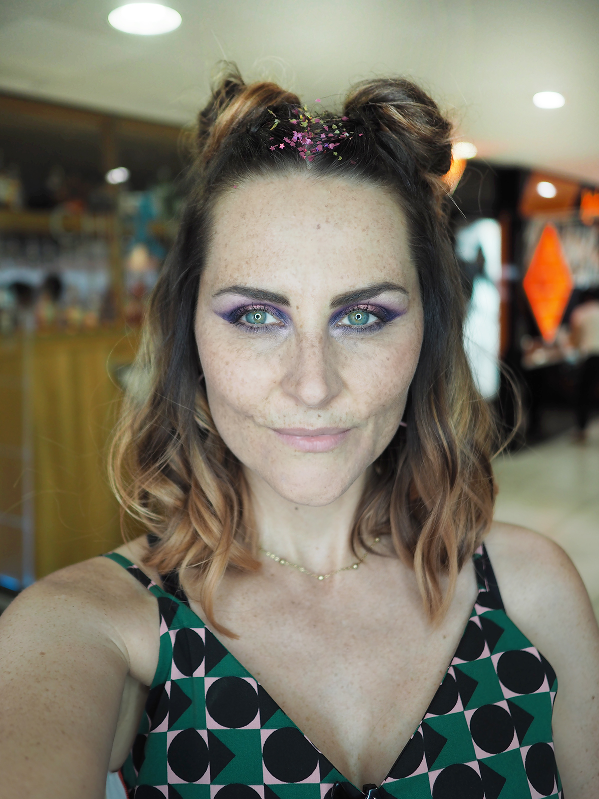 space bun hair with glitter festival makeup